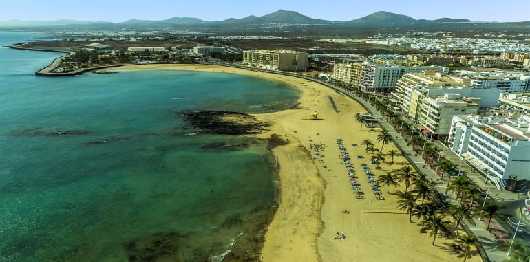 arrecife-aerial-view-of-playa-reducto-beach-cityscape-mountains-in-distance