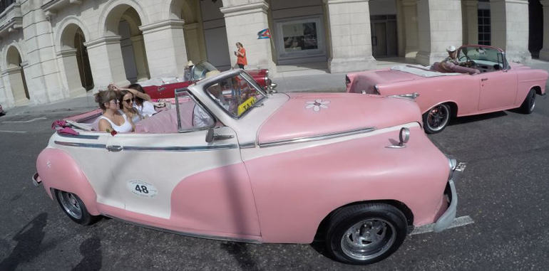 cuba-tourism-videos-pink-classic-american-cars-driving-in-old-havana