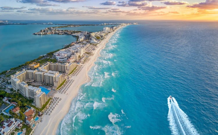 mexico-cancun-hotel-zone-aerial-view-resort-strip-pools-white-sand-turquoise-waters-motorboat-riding-into-sunset