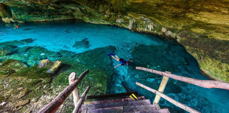 mexico-xel-ha-cenote-dos-ojos-stairs-leading-down-to-swimmers-snorkeling-in-clear-blue-water