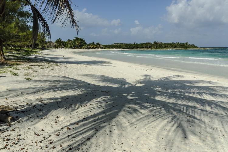 mexico-xpu-ha-beach-idyllic-white-sands-palm-trees-shadows-blue-waters-on-curving-peninsula