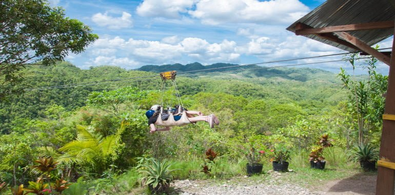 philippines-bohol-attraction-danao-adventure-parrk-zipline-tandem-couple-flying-into-jungle-canopy