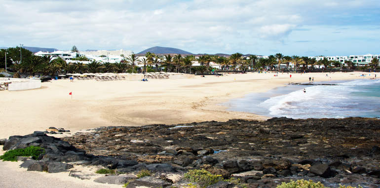 playa-cucharas-beach-golden-sand-rock-seabed-blue-water-palm-trees-hotels-in-distance